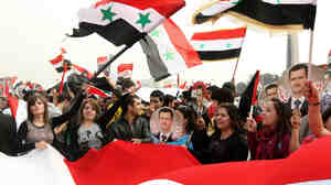 Tens of thousands of people rally in support of Syrian President Bashar al-Assad in Damascus on Wednesday.