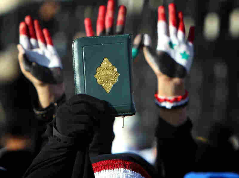A Yemeni woman in the capital Sana'a holds up a copy of the Quran while others raise their palms painted with the colors of the Yemeni (left), Libyan (center) and Syrian flags during a demonstration on Monday against President Ali Abdullah Saleh.
