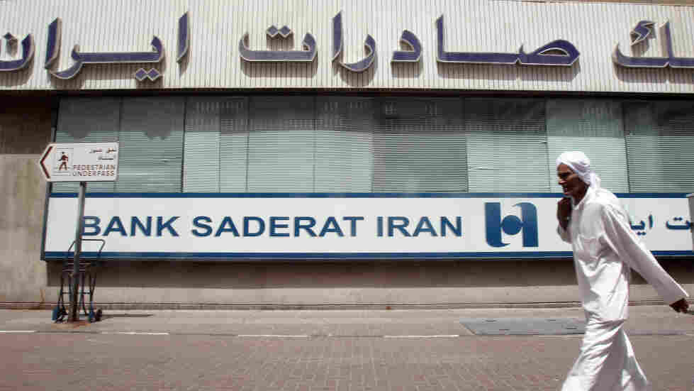 A man walks past a branch of Iran's Bank Saderat in Dubai, in the United Arab Emirates. An estimated $2.6 billion has been stolen from Bank Saderat and other leading Iranian banks, causing a growing scandal.
