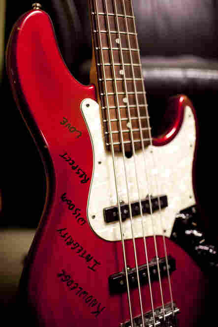 "Derrick Hodge's bass reads ""Knowledge, Integrity, Wisdom, Respect, Love."""