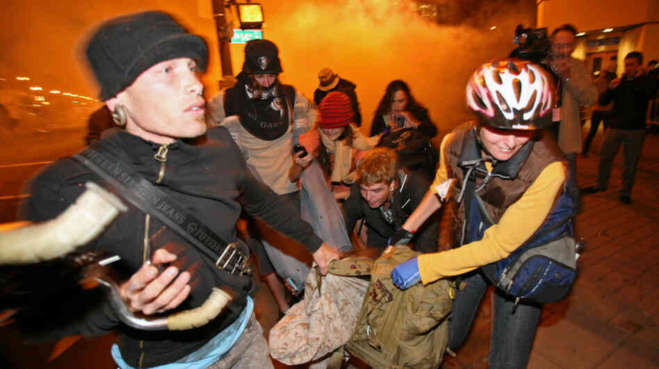 Occupy Oakland protesters carry away a man who was hit by a police tear gas canister Tuesday near the Oakland City Hall.