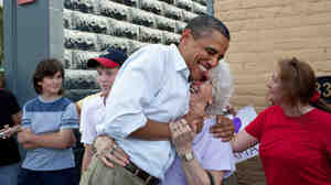 "President Barack Obama greets people outside the Old Market Deli in Cannon Falls, Minn., on the Aug. 15, during a Midwest bus tour. The same day he said he likes the term ""Obamacare."""