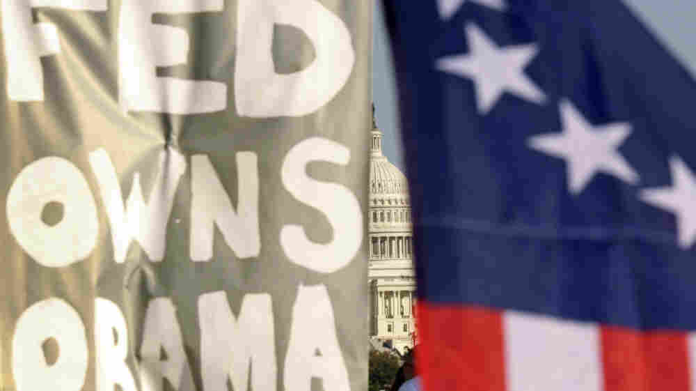"A sign at an Occupy D.C. protest reads ""Fed Owns Obama."" The president has so far had the worst of both worlds, with much of Wall Street convinced he's anti-business, and the protesters convinced he's in bed with the banks."
