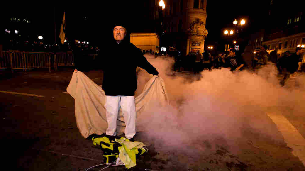 An Occupy Oakland protester stands with a banner after police used tear gas to disperse a large crowd Tuesday (Oct. 25, 2011).