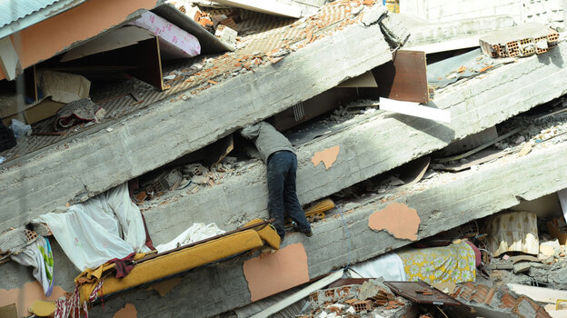A Turkish men searches through the debris of his collapsed building in Ercis.