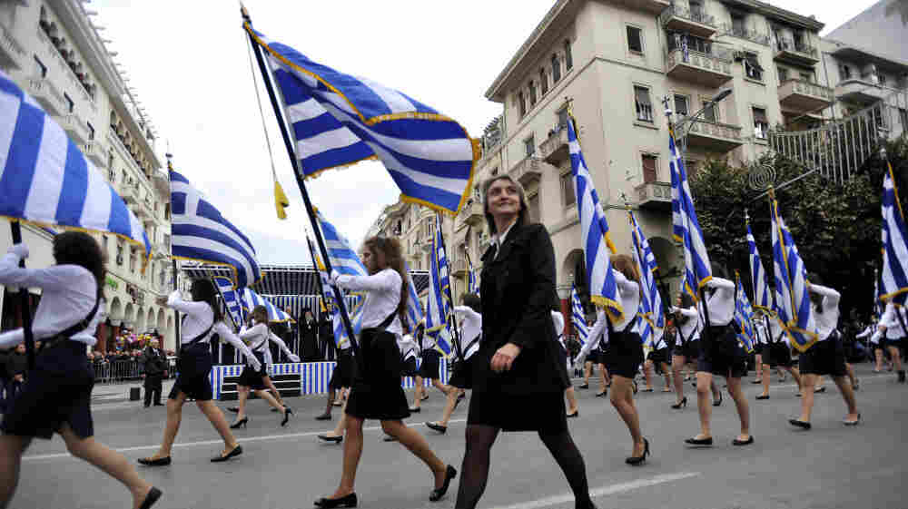 A teacher walks by during a parade in the northern Greek city of Thessaloniki on Thursday. Parades were held across Greece on Thursday to mark the 61st anniversary of the country's resistance to Axis forces, which dragged Greece into World War II. Some bystanders also seized the opportunity to shout anti-austerity slogans.