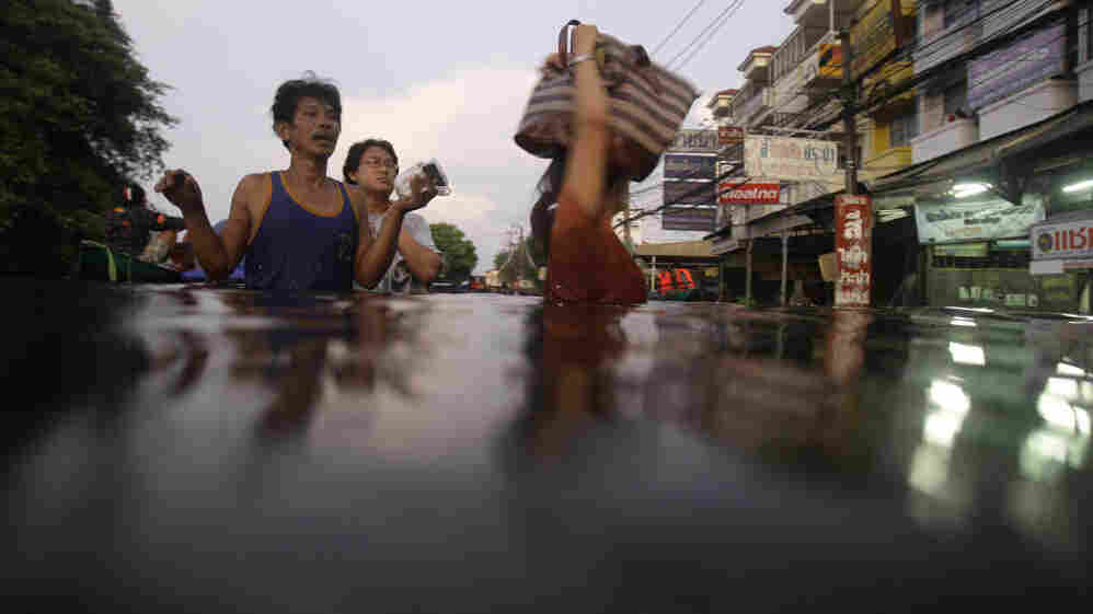 Residents wade along a flooded street on the outskirts of Bangkok on Thursday. Clambering aboard bamboo rafts and army trucks, residents fled their homes as high waters moved closer to the heart of the city.