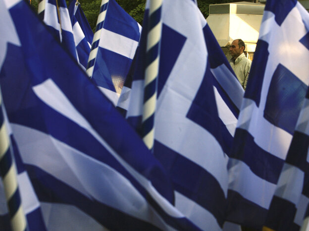 A pedestrian passes a vendor selling Greek flags in Athens on  Wednesday (Oct. 26, 2011). Greece's crushing debts triggered the latest crisis.