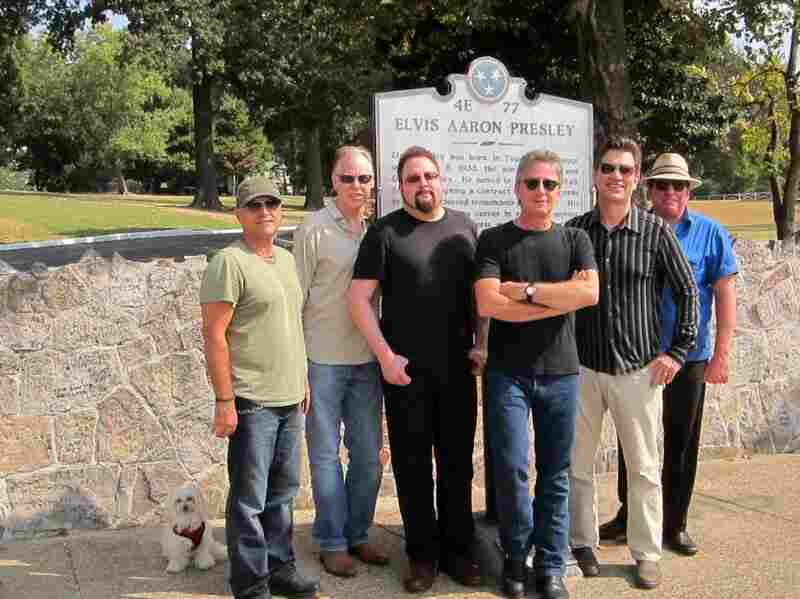 Rodney the Maltese dog takes a photo with the band at Graceland.