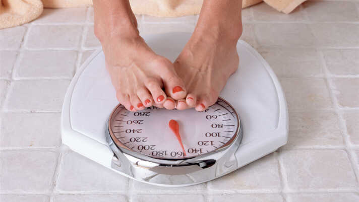A dieter checks weight on a bathroom scale.