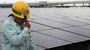 A worker stands next to an array of Sharp solar cell modules at a power plant south of Tokyo in August. Sharp was one of 1,400 solar panel manufacturers in attendance at the Solar Power International conference, where industry optimism was high.