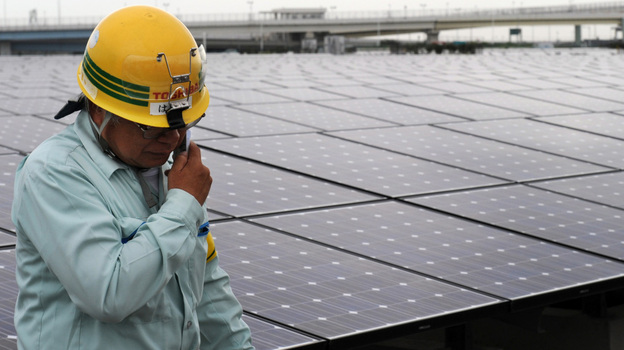 A worker stands next to an array of Sharp solar cell modules at a power plant south of Tokyo in August. Sharp was one of 1,400 solar panel manufacturers in attendance at the Solar Power International conference, where industry optimism was high. (AFP/Getty Images)