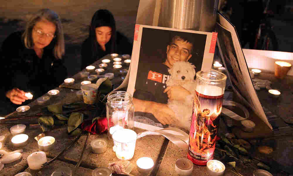 A photograph of Iraq War veteran Scott Olsen is seen Thursday at a vigil. Olsen was severely injured during a standoff between police and protesters in Oakland, Calif., two days earlier. He remains hospitalized.