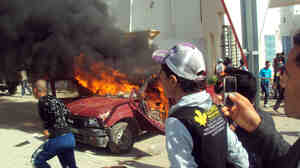 A car burns during clashes between demonstrators and secuitry forces on Friday in Sidi Bouzid.