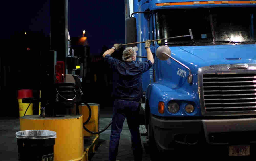 A truck driver cleans his windshield at a filling station in Milford, Conn. The long hours, weeks away from home and mediocre pay contribute to the trucking industry's shortage of an estimated 125,000 drivers.