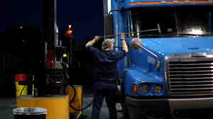 A truck driver cleans his windshield at a filling station in Milford, Conn. The long hours, weeks away from home and mediocre pay contribute to th