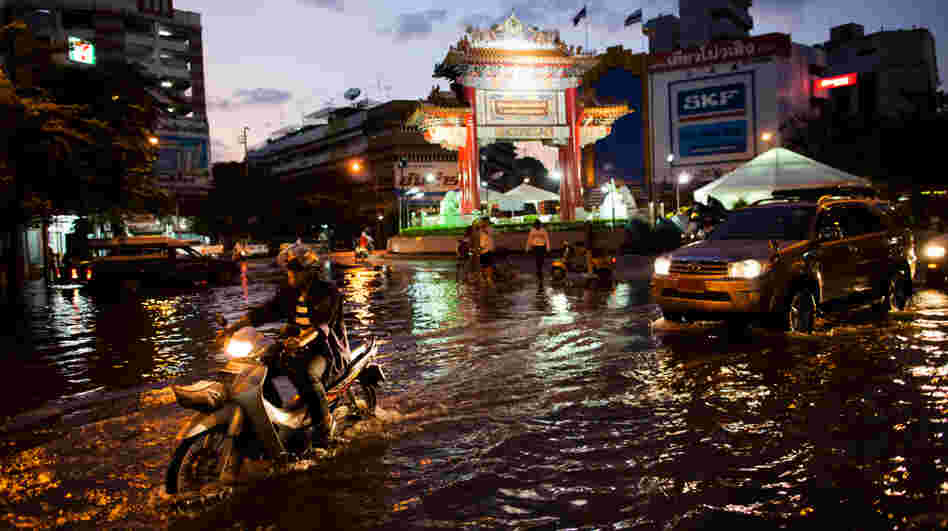 Residents drive through a flooded street close to the overflowing Chao Phraya river in Bangkok on Thursday. About 400 people have died from floods in the country since late July.