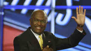 Herman Cain waves before a GOP debate at St. Anselm College in Manchester, N.H., in June. Pollster Andy Smith says most New Hampshire residents prefer having no broad-based income tax or sales tax.