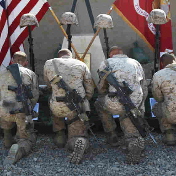 Marines with 3rd Battalion, 5th Marine Regiment, kneel before battlefield memorials for their fallen brothers during a farewell ceremony, Oct. 30, 2010.