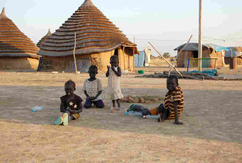 Children in South Sudan, one of the world's poorest nations, sit in front of traditional homes made of mud and thatch.