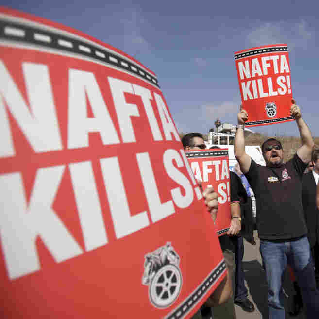 """Teamsters union members hold signs that read, """"NAFTA kills,"""" during a news conference by congressmen and union leaders against the cross-border trucking program Oct. 19 in San Diego."""