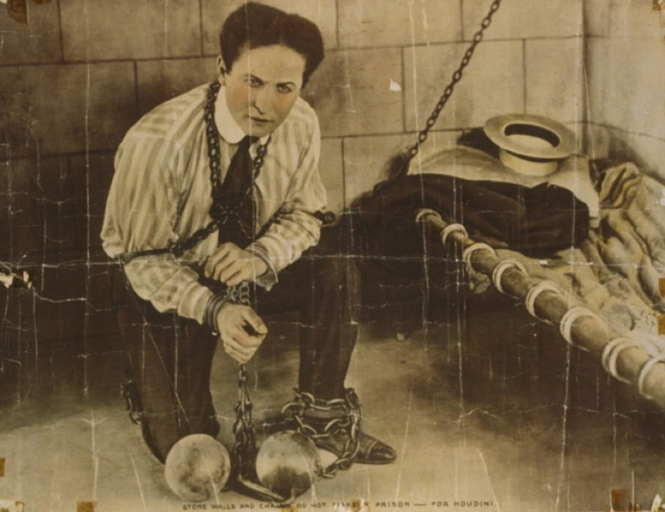 "Harry Houdini started performing as a professional magician in the U.S. in 1891. The caption at the bottom of this photo reads: ""Stone walls and chains do not make a prison — for Houdini.""  (NPR)"