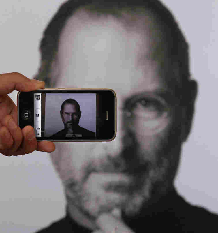 A photographer uses his iPhone to take a picture of a tribute to Apple co-founder Steve Jobs in front of an Apple store in London.