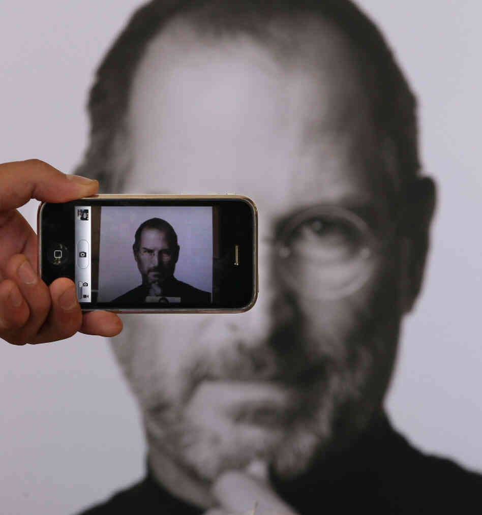 A photographer uses his iPhone to take a picture of a tribute to Apple co-founder Steve Jobs in front of an Apple store in London