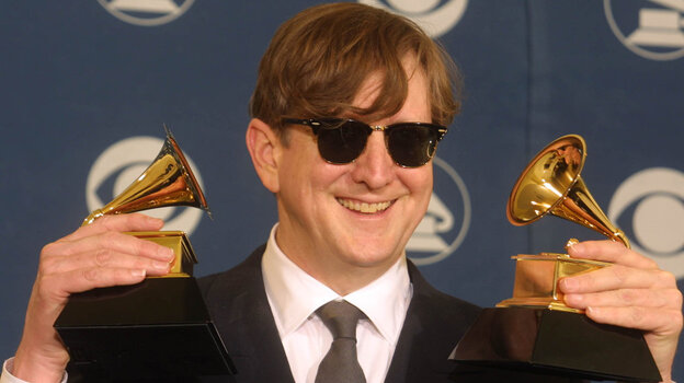 T Bone Burnett holds two trophies, one for Producer of the Year, at the Grammy Awards in 2002.