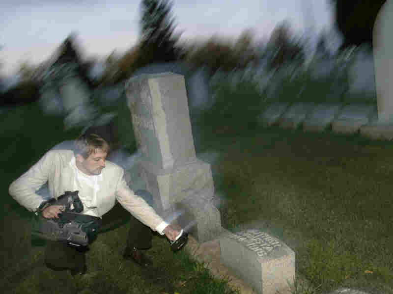 Paranormal investigator Noah Voss points a video camera at an electromagnetic frequency device to record any abnormal activity at the Sun Prairie Cemetery in Sun Prairie, Wis.