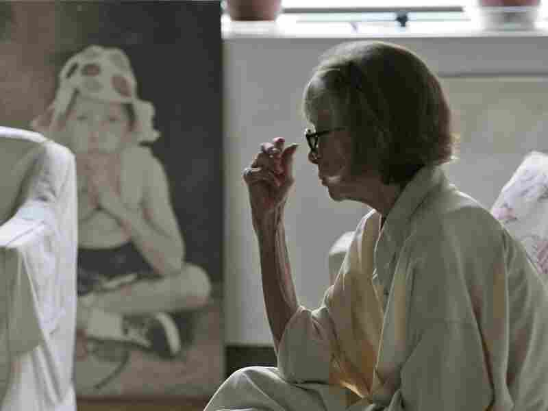 Didion looks at a painting of her daughter in her New York apartment.