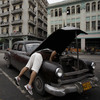 A man checks his car in Havana. In October, Cuba legalized the sale and purchase of automobiles for all citizens. Now, Cubans who leave the island permanently can transfer ownership of their car to a relative or sell it outright. Previously, Cuba could seize the vehicles of those who emigrated.
