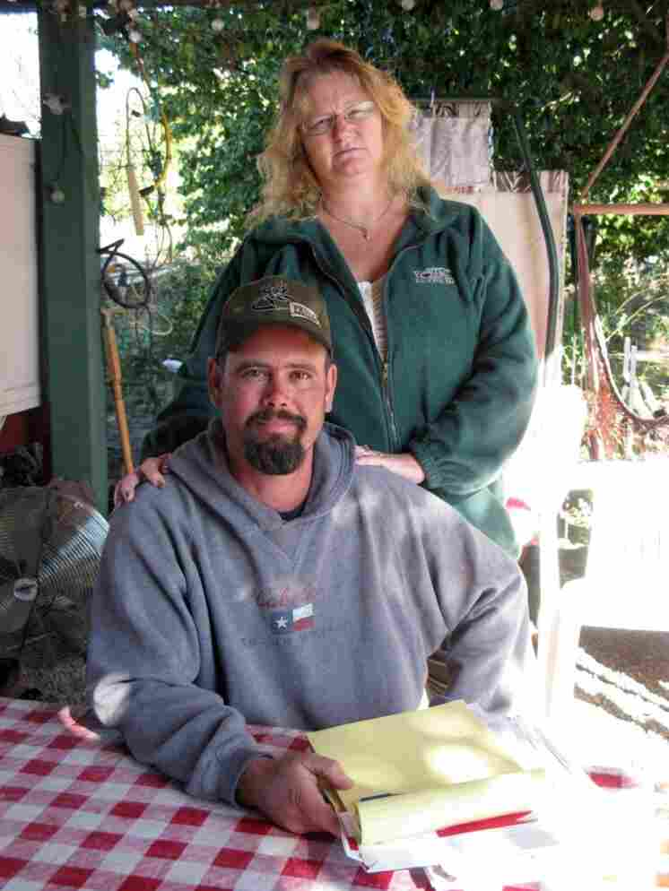 Craig and Linda Black sit at a table in the yard of their home in Vacaville, Calif. They are desperately trying to hang on to their home after falling behind on their mortgage payments.