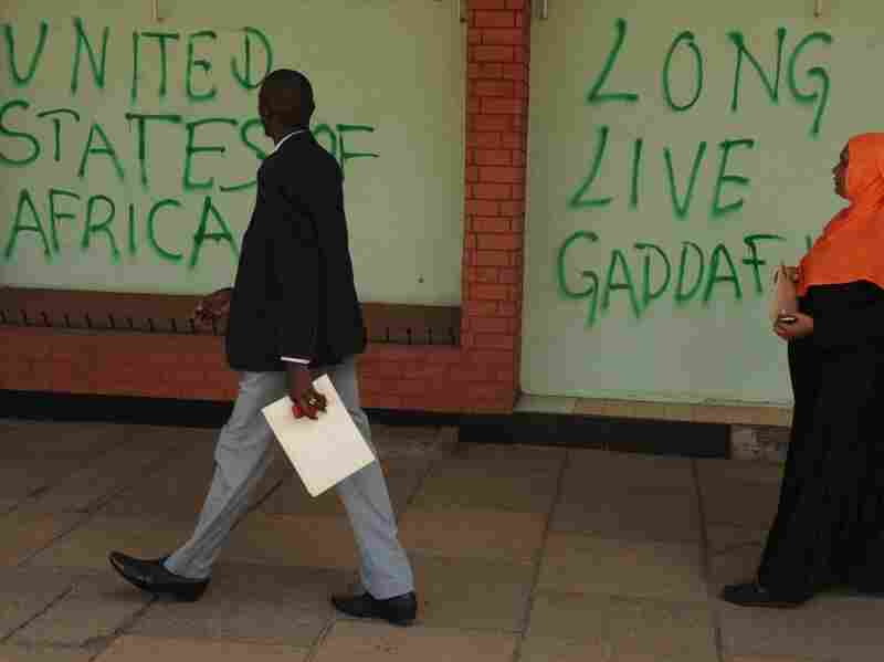People walk past grafitti on the wall of the Libyan Embassy in Nairobi on Oct. 31, 2011 after activists took to the streets in support of slain Libyan leader Moammar Gadhafi, whom they said should have been aprehended and handed to the relevant authorities during the fall of his hometown of Sirte.