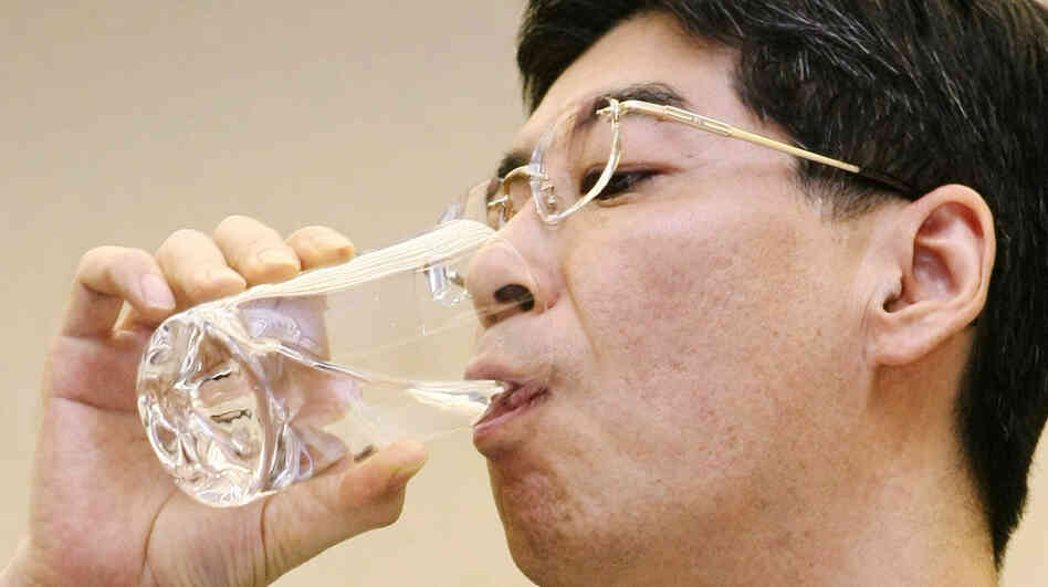 Japan's Parliamentary Secretary for the Cabinet Office Yasuhiro Sonoda drinks a glass of decontaminated water taken from puddles inside the buildings housing reactors 5 and 6 at the Fukushima No. 1 plant.