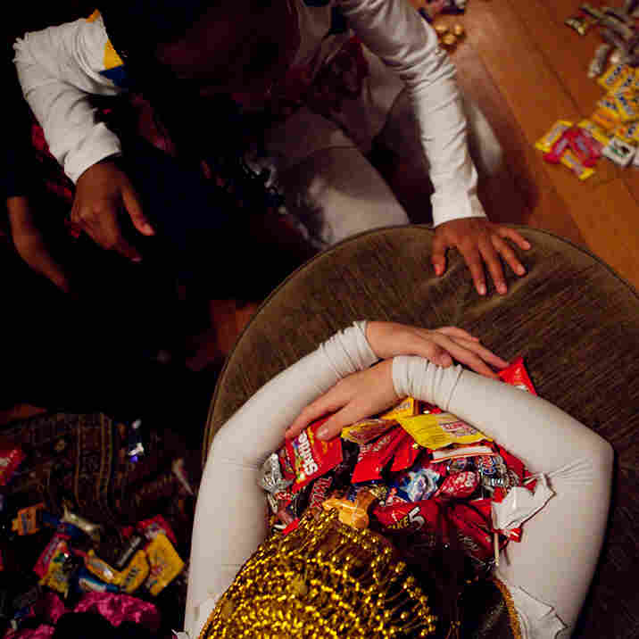 Sierra Lewter grabs a coveted candy after trick-or-treating on Halloween.
