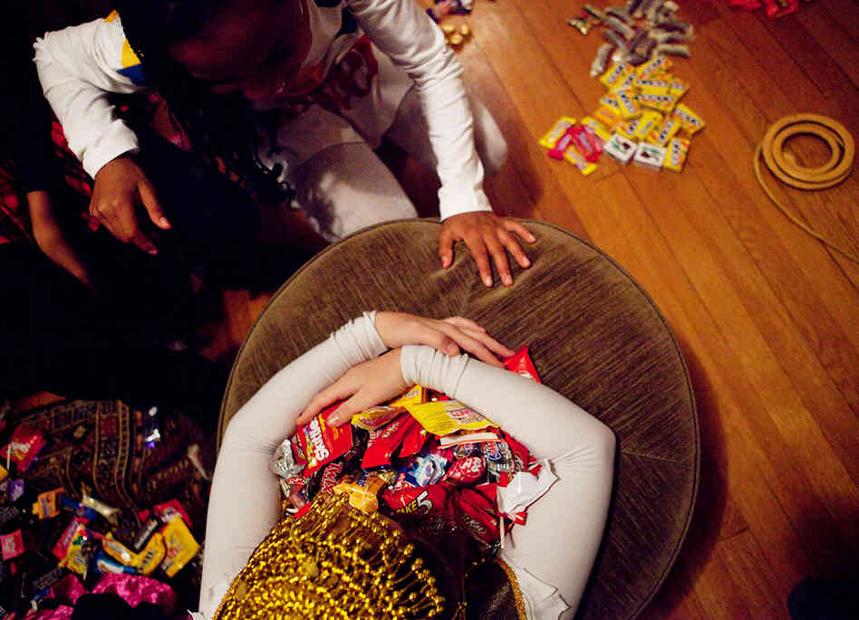 Eden Rose Breslow grabs her loot as Sierra Lewter goes in for a trade after trick-or-treating on Monday.