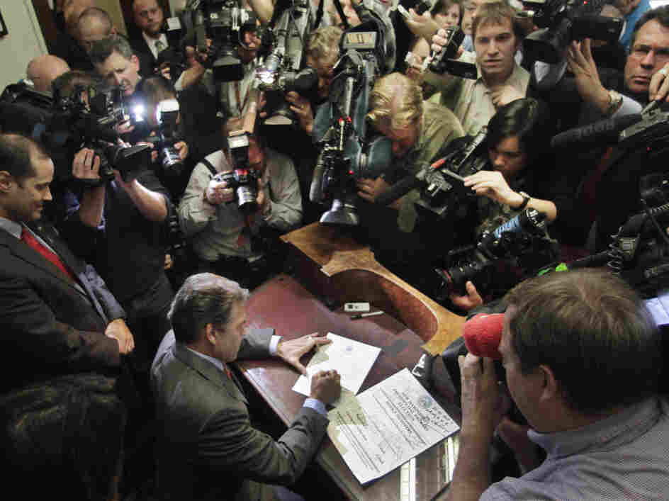 Texas Gov. Rick Perry fills out his papers to be on the New Hampshire's presidential primary ballot, Friday, Oct. 28, 2011.