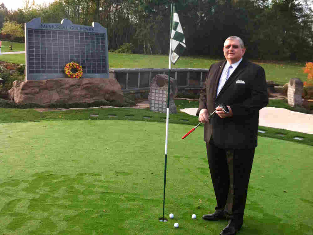 """Memorial Golf Park creator Arne Swanson stands on its putting green — an ossuary with enough capacity to hold 600 former avid golfers. Families can purchase a spot on the solemn """"leader board"""" to preserve the loved one's standing for all eternity."""
