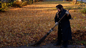 An elderly woman rakes leaves in Kaliningrad, Russia. Since 1992, the number of deaths in the country has outpaced births by nearly 3 to 2.