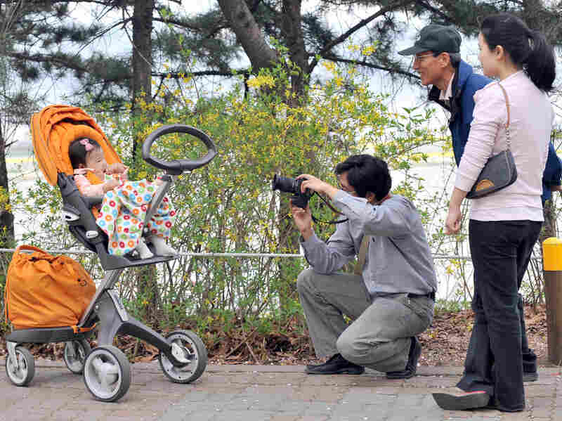 A South Korean man takes a photo of his baby during a picnic in Seoul, in 2009. After years of promoting family planning, South Korea is seeing unprecedented numbers of women staying single into their 30s — up from a handful a generation ago to 40 percent.