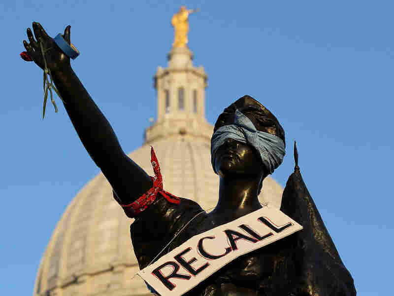 "A sign that reads ""recall"" hangs on a statue in front of the Wisconsin state Capitol last month in Madison. Labor groups are making an effort to recall Gov. Scott Walker for his controversial union rights law."