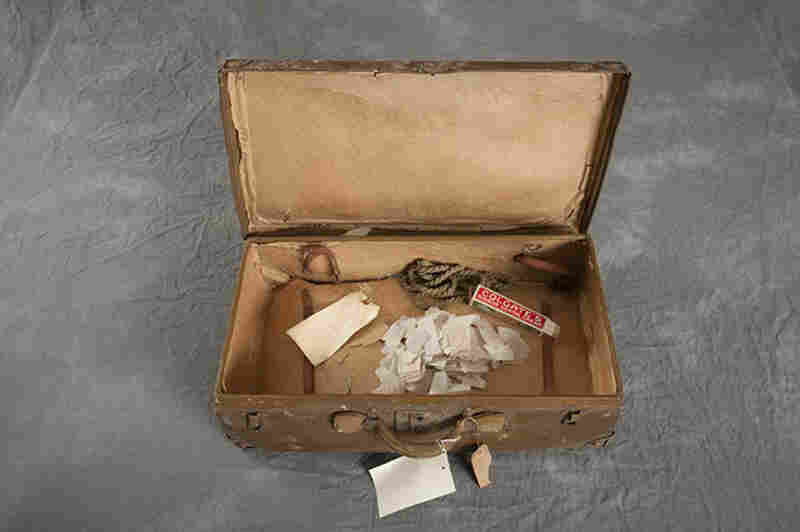 This suitcase, belonging to Raymond H., has a tag that dates it to May 4, 1923.