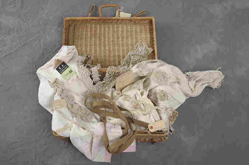 A wicker suitcase belonging to Mary Watson contains fabrics and lace.
