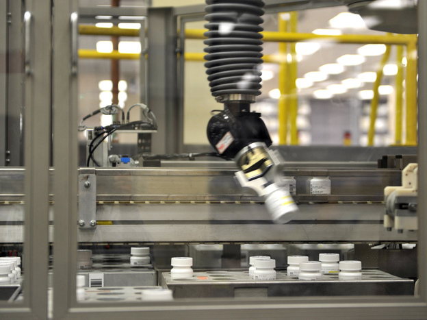 An automated robot arm picks up a bottle of prescription pills in the Medco pharmacy plant in Willingboro, N.J. Medco's state-of-the-art automated pharmacy can dispense up to 1 million prescriptions a week.