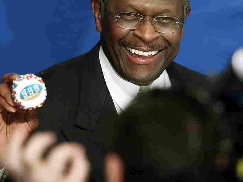 Republican presidential candidate Herman Cain holds up a cupcake decorated with his 9-9-9 economic pland before a speech at the National Press Club Oct. 31, 2011 in Washington, DC.