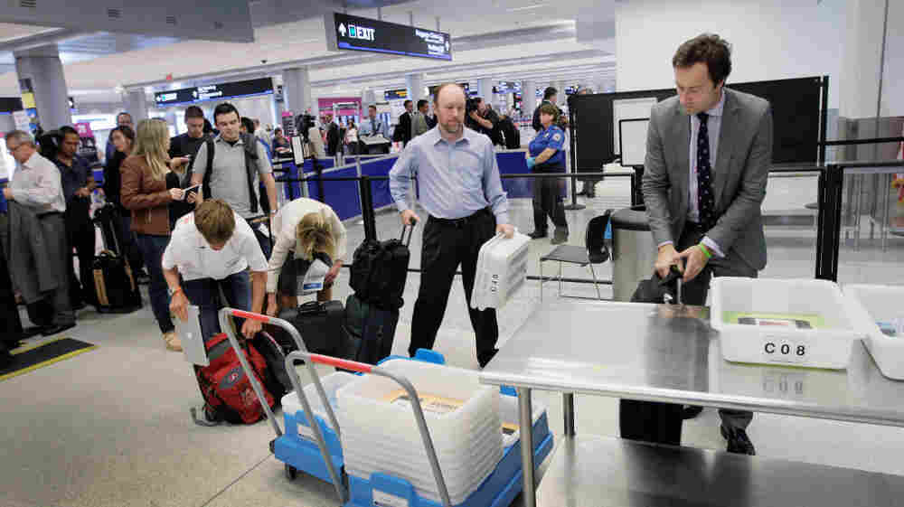 Passengers wait to clear security next to the newly opened pre-check lane at Miami International Airport. The airport is one of four that is allowing frequent fliers to use a special security line where they can keep their shoes on and their laptops in their bags.