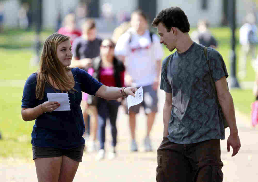 Genna Schwartz (left) of the Ohio State University Student Democrats tried to hand out information about President Obama's Oct. 17 visit to Ohio State and was turned down by a young man. The Obamamania that gripped college campuses two years ago is largely gone.