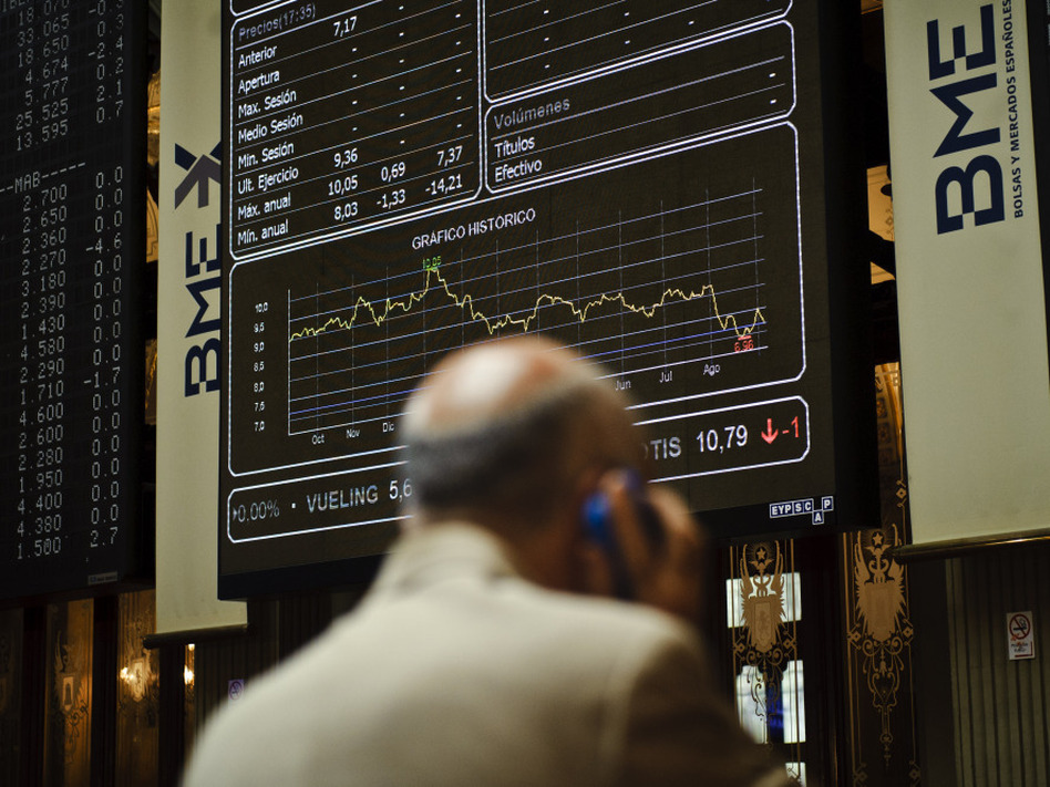 "A broker uses a phone in front of the main screen at the Stock Exchange in Madrid, Spain. The country's central bank recently warned of ""troubled exposure"" to real estate, heightening fears about the stability of Spain's banks."