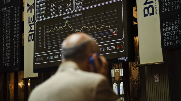 """A broker uses a phone in front of the main screen at the Stock Exchange in Madrid, Spain. The country's central bank recently warned of """"troubled exposure"""" to real estate, heightening fears about the stability of Spain's banks. (AP)"""